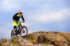 骑自行车的专业骑自行车者在岩石的上面 极端体育概念 文本的空间 免版税库存照片