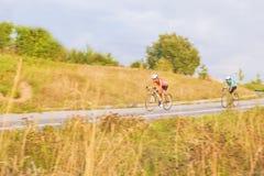 骑自行车的两个女性白种人女运动员的训练过程 库存照片
