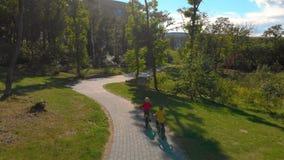 骑自行车的两个小男孩空中射击在公园 股票录像