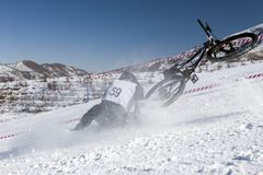 骑自行车的人下坡山雪冬天 免版税图库摄影