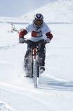 骑自行车的人下坡雪 免版税库存照片