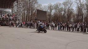 骑自行车的人乘坐在摩托车和,当驾驶时跃迁背面在位子并且继续 在自行车的困难的把戏 股票视频
