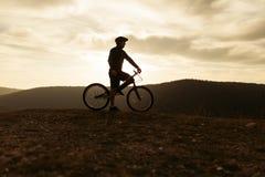 骑自行车的人剪影小山的 免版税库存照片