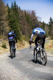 骑自行车的人去的山上升 免版税库存照片
