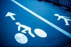 骑自行车的人和步行者的标志蓝色的 库存图片