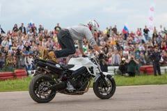 骑自行车的人在摩托车的爬的脚 免版税库存图片