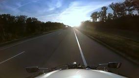 骑自行车的人在摩托车的高速公路乘坐遇见太阳 股票录像