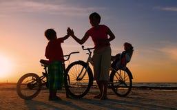 骑自行车的人在日落的家庭剪影,有两个孩子的母亲在自行车 图库摄影