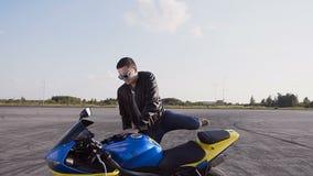 骑自行车的人在皮夹克和牛仔裤打扮,去他的摩托车,下来坐他并且戴太阳镜 股票录像