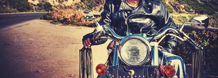 骑自行车的人在葡萄酒的正面图和摩托车定调子 免版税库存照片