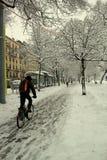 骑自行车的人城市雪 库存照片