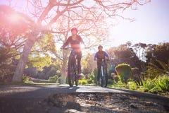 骑自行车的人夫妇低角度视图循环在乡下路的 库存图片