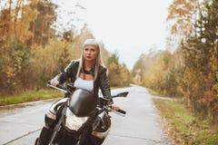 骑自行车的人女孩在雨中骑一辆摩托车 最初人员查阅 免版税库存图片