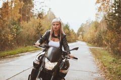骑自行车的人女孩在雨中骑一辆摩托车 最初人员查阅 免版税库存照片
