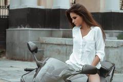 骑自行车的人女孩在雨中骑一辆摩托车 最初人员查阅 图库摄影