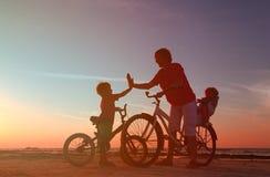骑自行车的人家庭剪影,有两个孩子的父亲在自行车 免版税库存照片