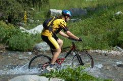 骑自行车的人小河山 免版税库存图片