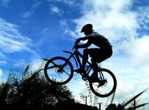 骑自行车的人山剪影 免版税库存照片