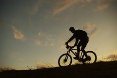 骑自行车的人山剪影 图库摄影