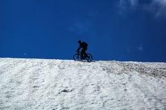 骑自行车的人山天空雪 免版税库存图片