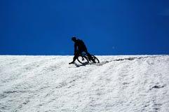 骑自行车的人山天空雪 免版税库存照片
