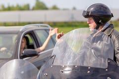 骑自行车的人显示他的中指对汽车司机 库存照片