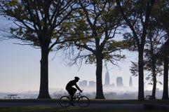 骑自行车的人有雾的早晨 免版税库存图片