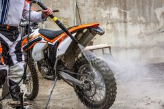 骑自行车的人洗涤一辆摩托车 库存图片