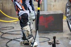 骑自行车的人洗涤一辆摩托车 库存照片