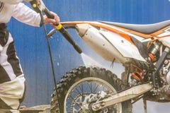 骑自行车的人洗涤一辆摩托车 免版税图库摄影