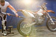 骑自行车的人洗涤一辆摩托车 免版税库存照片