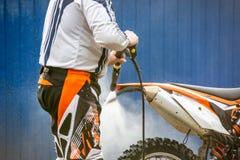 骑自行车的人洗涤一辆摩托车 免版税库存图片
