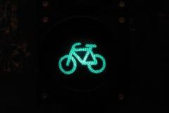 骑自行车的人的绿灯在夜之前 免版税库存照片