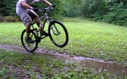 骑自行车的人自行车前轮离地平衡特技 库存照片