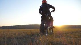 骑自行车的人被停下来在领域等待他的朋友 草甸的运动员 享受在他的摩托车的人乘驾 影视素材