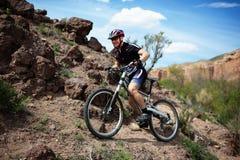 骑自行车的人通配沙漠的山 库存图片