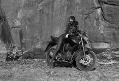 骑自行车的人题材:有摆在与motorbik的面具的美丽的性感的妇女 免版税图库摄影
