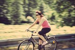 骑自行车的俏丽的妇女 库存照片