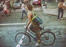 骑自行车的可爱的妇女在街道 免版税库存图片