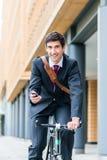 骑自行车的多任务年轻商人工作 库存图片