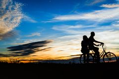 骑自行车的夫妇剪影在日落 免版税库存图片