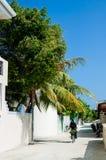 骑自行车的妇女在一个小热带海岛的狭窄的街道 Kuda Huraa海岛,马尔代夫 库存照片