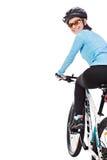 骑自行车的妇女骑自行车者回顾和微笑 免版税库存照片
