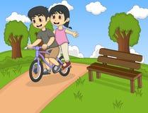 骑自行车的孩子在公园动画片 免版税图库摄影