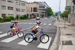 骑自行车的孩子学校 免版税库存照片