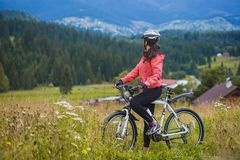 骑自行车的少妇在高原 免版税图库摄影