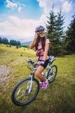 骑自行车的少妇在高原 库存照片