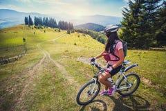 骑自行车的少妇在高原 库存图片