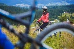 骑自行车的少妇在高原 免版税库存照片