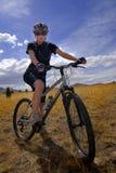 骑自行车的山妇女年轻人 免版税库存照片